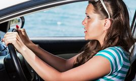 Fright face of woman in the car. She is scared and shocked by driving car stock image