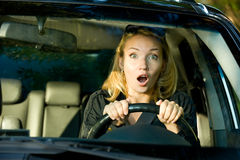 Fright face of woman driving car. And strongly squeeze the wheel stock image