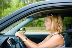 Fright face of woman sitting in car. Profile face of fright woman sitting in the car and holds the wheel - outdoors stock image