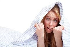 Fright at night. Blond woman covering her head with the duvet stock photography