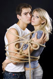 Frighten couple bound with ropes. Cord fastened by a bow stock photo