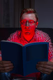 Frighten man reading horror. In dark room Royalty Free Stock Photo