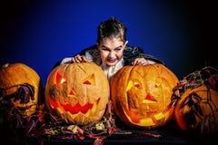 Frighten vampire. Little boy in halloween costume of vampire posing with pumpkins. Over dark background royalty free stock images