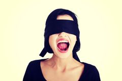 Frighten young blindfold woman screaming. Portrait of a beautiful frighten young blindfold woman screaming Stock Images