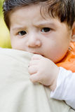 Frightened baby boy. Close up of a cute frightened baby boy hiding behind mommy's shoulder Stock Photography