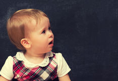 Frightened baby girl with chalk at a school board Royalty Free Stock Images