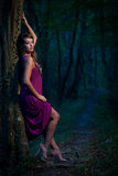 Frightened Beautiful lady on a forest path at dusk Stock Photography