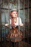 Frightened beautiful steampunk woman in the cage Royalty Free Stock Photos
