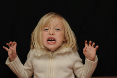Frightened blond girl. A portrait of a young blond girl wearing a white jacket against a black background, holding both hands and arms up as if very frightened stock photos