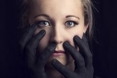 Frightened blonde woman grabbed by black hands on face. Frightened blonde woman grabbed by black hands on her face Royalty Free Stock Photo