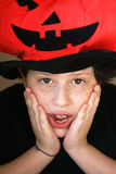 Frightened boy with pumpkin hat. Frightened boy with red pumpking hat royalty free stock photos