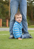 Frightened boy sits at feet of adult Stock Photos