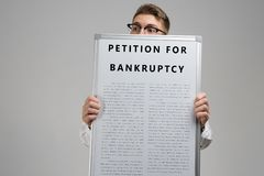 Young man keeps in front of him petition for bankruptcy isolated on light background. Frightened Business man with glasses holds a poster with a petition for royalty free stock photos