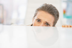 Frightened business woman looking out from desk Royalty Free Stock Images