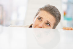 Frightened business woman looking out from desk Royalty Free Stock Photography