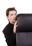 Frightened businessman. Hiding behind a chair Stock Image