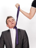Frightened businessman being pulled by the tie Stock Images