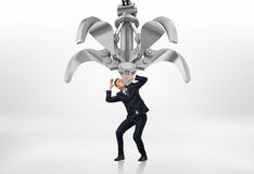 Frightened businessman in protective pose looking up at giant mechanical claw above him. A frightened businessman in a protective pose looking up at the giant Royalty Free Stock Images