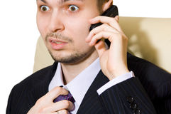 Frightened businessman talking over the phone Royalty Free Stock Image