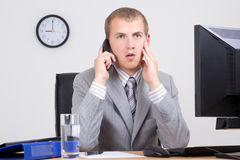 Frightened businessman talking on phone in office Stock Photo