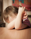 Frightened child. Closed his hands over eyes royalty free stock image