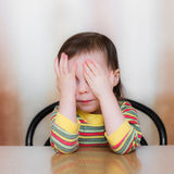 Frightened child. Closed his hands over eyes stock image