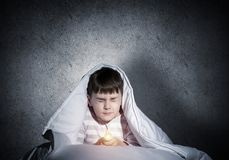 Frightened child with flashlight under blanket. Frightened child with flashlight hiding under blanket. Scared kid with closed eyes lying in bed at home. Little royalty free stock image
