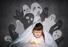 Frightened child with flashlight under blanket. Frightened child with flashlight hiding under blanket. Scared kid with closed eyes lying in bed at home. Little stock photos