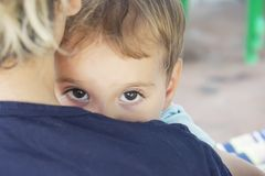A frightened child hides behind his mother. A frightened child hides behind a mother close up stock photos