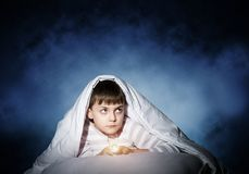 Frightened child hiding under blanket. Frightened child with flashlight hiding under blanket. Scared kid lying in his bed at home. Fear of the dark. Little boy stock photography