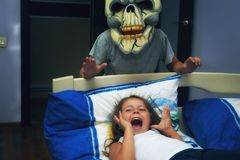 Frightened child at night in bed. A terrible night dream of a child. Invented children`s fears. Brother scares her sister at night stock photo