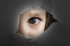 Frightened child. Is spying through a hole in wall stock photography