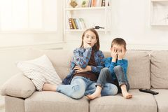 Frightened children watching TV at home. Frightened children watching scary movie at home, brother and sister having rest without parents, copy space Royalty Free Stock Images