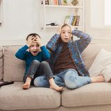 Frightened children watching TV at home. Frightened children watching scary movie at home, brother and sister having rest without parents, copy space Royalty Free Stock Photography