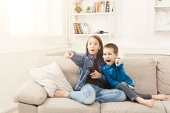 Frightened children watching TV at home. Frightened children watching scary movie at home pointing at tv set, brother and sister having rest without parents Stock Photo