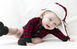 Frightened Christmas baby falling over. Surprised Christmas baby with red plaid shirt and furry wool hat falling over while trying to pull off cap Stock Photos