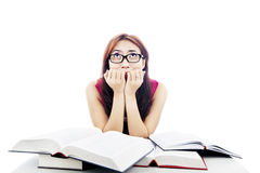 Frightened college student. Portrait of frightened female college student with textbooks biting her nails Stock Photo