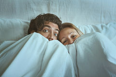 Frightened couple with eyes wide open. Under the sheets. Fear and shock concept Stock Images