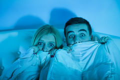 Frightened couple at home. Frightened couple watching a horror movie stock photos