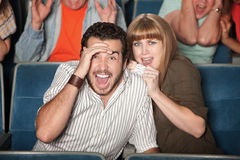 Frightened Couple in Theater. Scared couple screaming out loud watch horror movie Royalty Free Stock Image