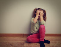 Frightened crying kid girl sitting on the floor with closed face Stock Photography