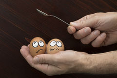 Frightened egg face in man hand and spoon Stock Photo