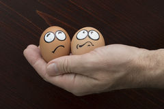 Frightened egg face in man hand Stock Photos