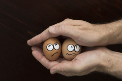Frightened egg face in man hand Royalty Free Stock Photos