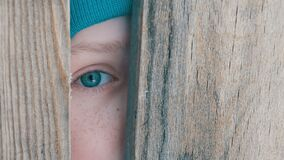 Frightened eye of a teenage boy peeks into the door slot or crevice in the fence. The frightened eye of a teenage boy peeks into the door slot or crevice in the stock footage