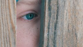 Frightened eye of a teenage boy peeks into the door slot or crevice in the fence. The frightened eye of a teenage boy peeks into the door slot or crevice in the stock video