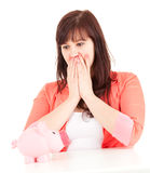 Frightened fat young woman with piggy bank Stock Image