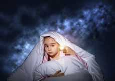 Frightened girl with flashlight under blanket. Frightened girl with flashlight hiding under blanket. Scared kid lying in his bed at home. Night terrors of child royalty free stock photos