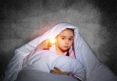 Frightened girl with flashlight under blanket. Frightened girl with flashlight hiding under blanket. Scared kid lying in his bed at home. Night terrors of child stock photography