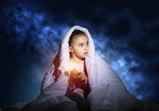Frightened girl with flashlight under blanket. Frightened girl with flashlight hiding under blanket. Scared kid lying in his bed at home. Night terrors of child stock images